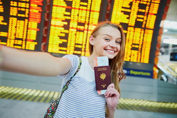 Tourist girl in airport, taking funny selfie with passport