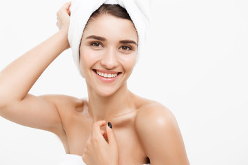 Beauty & Skin care concept - Beautiful caucasian Young Woman with bath towel on head covering her breasts, on white