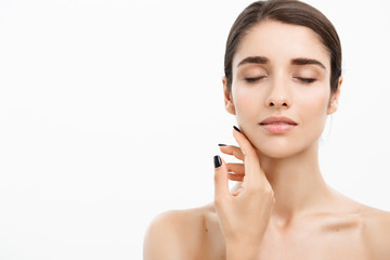 Beauty & Skin care concept - Close up Beautiful Young Woman touching her skin on white background.
