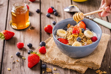 breakfast cereal shot on linen cloth wood boards angled view with raspberries blueberries sliced bananas strawberries with hand swirling honey landscape