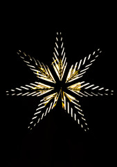 Photo of a golden star with light bulbs on a black background