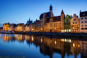 Scenic view of old buildings along the Long Bridge waterfront and their reflections on the Motlawa river at the Main Town in Gdansk, Poland, in the evening.