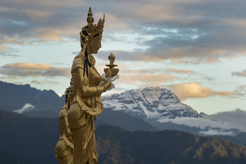 Goddess Statue near the Dordenma Golden Buddha, Thimphu with Himalayan peaks in the background.