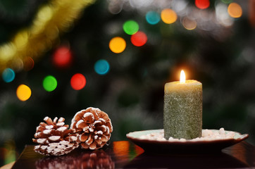 Christmas picture with a lit candle and pine cones