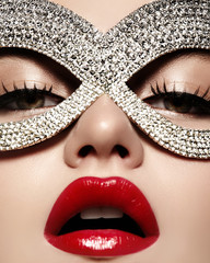 Beautiful Model with Fashion Lips Makeup wearing bright brilliant mask. Masquerade style woman. Holiday celebration look