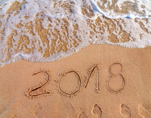 2018 written on sandy beach New Year is coming  like date holiday concept