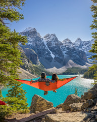 Lovers Sit in a Hammock Next to Beautiful Lake and Snowy Mountains