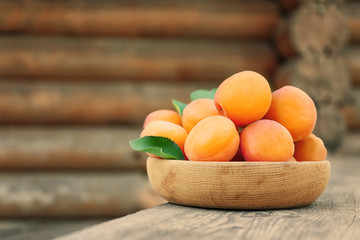 Juicy apricots in bowl on table outdoor