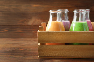 Crate with bottles of yummy smoothie on wooden table