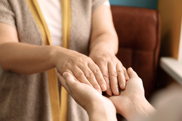 Young woman holding hands of her mother, closeup. Concept of care and support