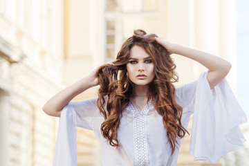 Outdoor portrait of young attractive woman with beautiful long curly hair. Model looking at camera, posing in street. Copy, empty space for text. Female fashion, beauty concept