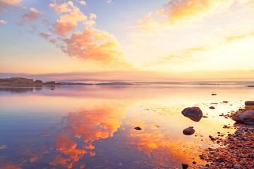 Breathtaking sunrise seascape scenery over Northern sea in Sweden. Epic dawn sea landscape. Lilac and red yellow colors scene.