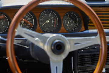 interior shot of vintage German sportscar with wooden steering wheel and trim