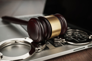 handcuffs and judge gavel on computer cyber crime concept