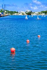 Orange Floats Leading Toward Sailboats