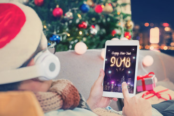 Man celebrate new year 2018 fireworks with tablet,Happy people lay on sofa and countdown from home with christmas tree at night,Holiday celebration with technology.
