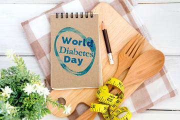 Notepad with World Diabetes Day text on the chopping board with wooden fork and spoon and the measuring tape , Diabetes world day on 14 November encourage awareness campaign background concept