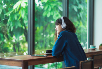Happy asian casual woman listening music with headphones near window at cafe restaurant,Digital age lifestyle,chill out  life