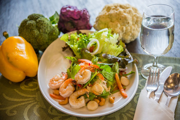 Dish of Thai style salad with cutlery, glass of water