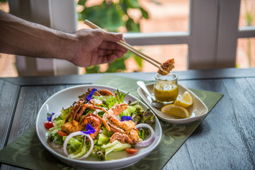 Hand with chopstick holding piece of crab Dish of salad with fried crab and orange sauce with on wooden table in restaurant