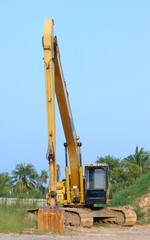 Heavy yellow excavator with long boom standing on floor sand.