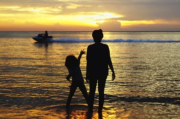 mother and daughter in silhouette against jet ski and beach during sunset