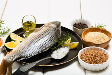 Healthy food diet river fresh raw fish omega 3 on pan with olive oil spoon of sea salt peppercorns grains lentils quinoa beans peas rosemary leaves on white wooden table background top view copy space