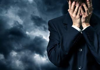 Businessman in despair on stormy sky