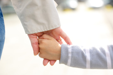 Mother and child holding hands outdoors