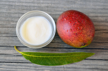 Mango body butter in a glass bowl and fresh ripe organic mango fruit and leaf on old wooden background.Spa,organic cosmetic or healthcare concept.Selective focus.