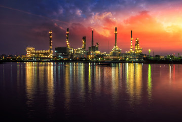 Oil and gas industry - refinery at Sunrise - factory - petrochemical plant with reflection over the river