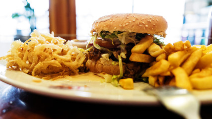 Unhealthy meal with mexican nacho chips, beef burger, loaded with cheese, fries, onion rings