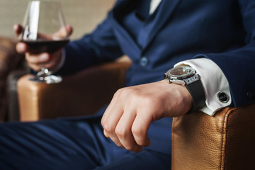 Groom holding glass of whiskey sitting on the chair, close up view Wall mural