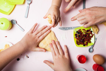 Mom teaches young children how to cook. Hands knead the dough, children's utensils.