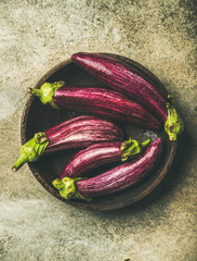 Flat-lay of fresh raw Fall harvest purple eggplants or aubergines in wooden bowl over concrete stone background, top view. Healthy Autumn vegan cooking ingredient