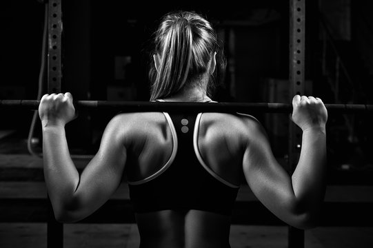 Back view young female doing barbell squats in gym