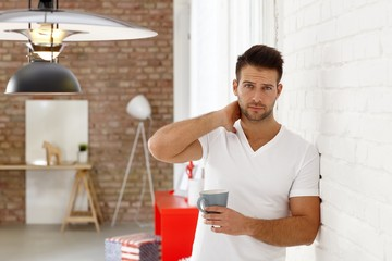 Young man frowning with morning tea in hand