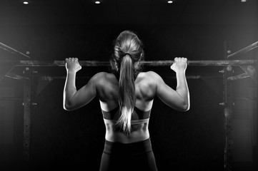 Young fitness female doing pull ups exercise Wall mural