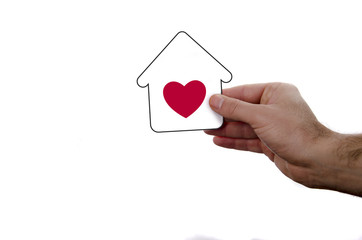 isolated hand holding dream house icon with red heart over a white background.