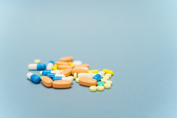Heap of colorful pills on blue background, selective focus