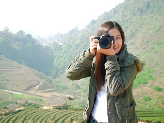 Asian tourist woman backpacker taking photo at mountain nature view ,Chiang Mai , Thailand on holiday vacation. tea plantation at background