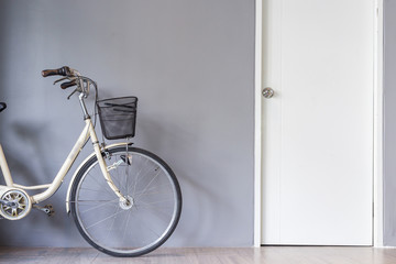 Bicycle parking near the grey wall and white door