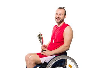 sportsman in wheelchair holding trophy