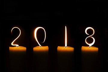 2018 written with candle flames on black background
