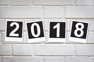 2018 in instant photo frames on a brick wall