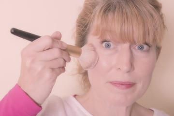 woman applying Blusher cosmetic
