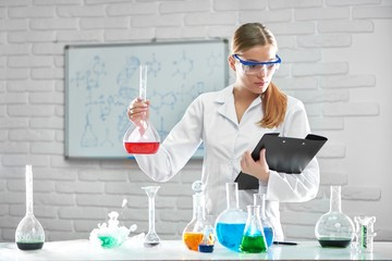 Shot of a beautiful young female researcher in a labcoat and protective eyewear reading her notes on a clipboard holding a flask with red chemical liquid copyspace research experiment scientific.