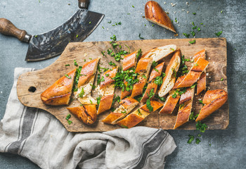 Turkish oriental pizza pide with cheese and spinach chopped in slices on wooden board over grey stone background, top view