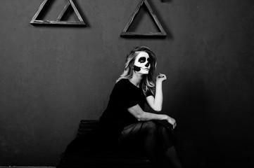 Halloween skull make up girl wear in black against blue wall at studio.