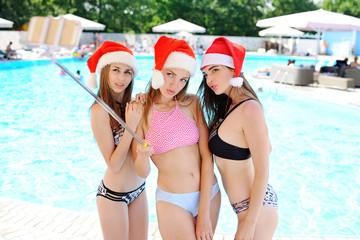 Three girls in bathing suits and caps of Santa Claus on a background of selfie shoot pool. Christmas vacation